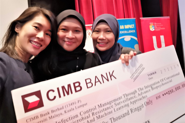 Dr Michelle Lee with two of her collaborators, microbiologist Dr Azmiza Syazwani Jasni and computer scientist, Dr Unaizah Hanum Obaidellah with their mock cheque.